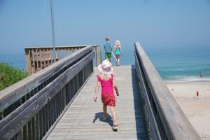 Kinder stehen am Strand auf einem Holzsteg